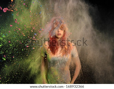 Redhead girl with colored powder exploding around her and into the background. - stock photo