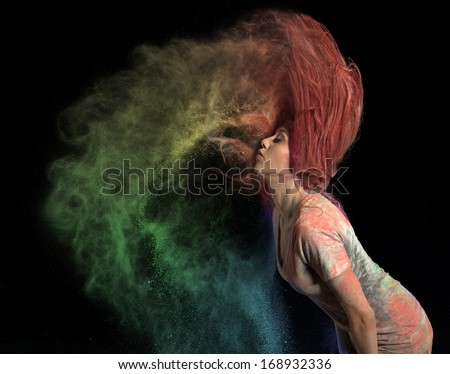 Redhead girl with colored powder trailing behind her hair that she is flinging up.  - stock photo