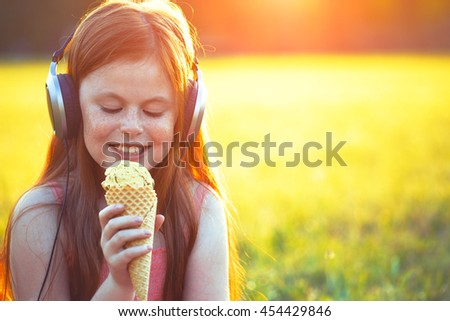 redhead girl with freckles eating ice cream and listening to music in headphones - stock photo