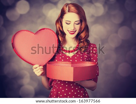 Redhead girl with gift for Valentines Day. Photo with bokeh at background - stock photo