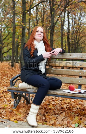 redhead girl with headphones listen music on player in city park, fall season - stock photo