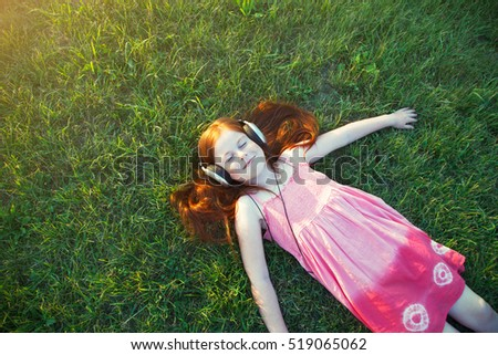 redhead girl with headphones listening to music. view from above. space for text
