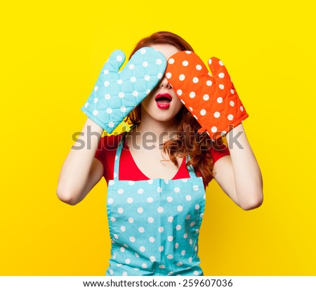 Redhead girl with oven gloves and apron on yellow background - stock photo