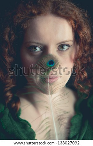 Redhead girl with peacock feather - stock photo