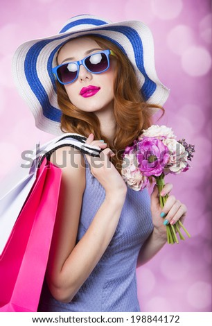 Redhead girl with shopping boxes and flowers on pink background. - stock photo