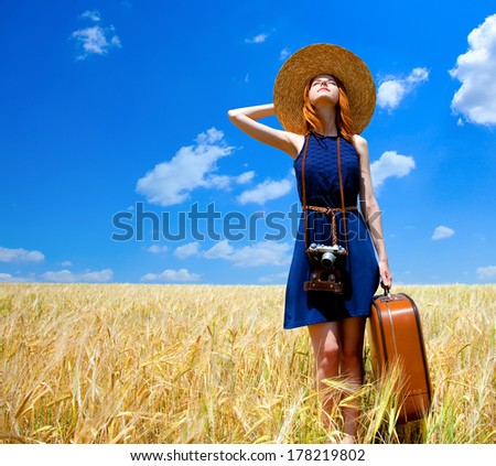 Redhead girl with suitcase at spring wheat field. - stock photo