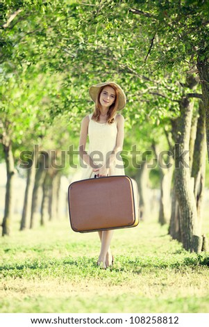 Redhead girl with suitcase at tree's alley.