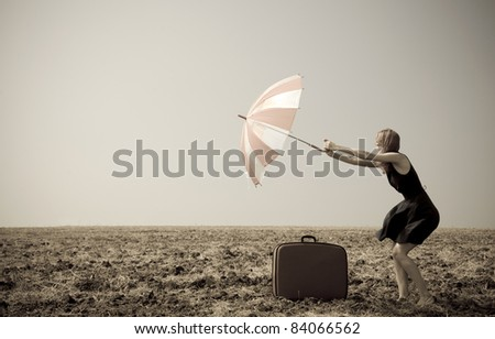 Redhead girl with umbrella at windy field. Photo in old image style. - stock photo