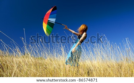 Redhead girl with umbrella at windy grass meadow - stock photo