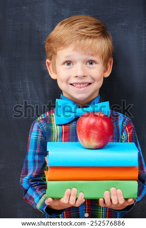 Redhead pupil expressing inspiration and positivity with multicolor book and an apple, diligent student concept - stock photo