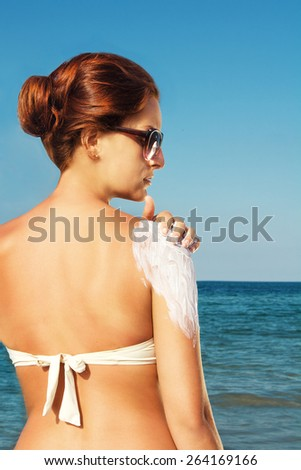 redhead rubs cream on her shoulder on the beach - stock photo