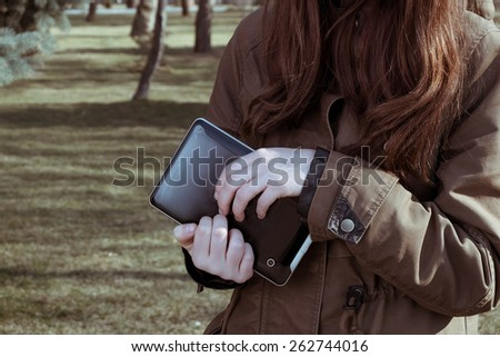 Redhead teen girl holding tablet pc in her hands outdoor in city park a lot of copyspace toned colorized image - stock photo
