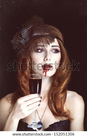 Redhead vampire woman with glass of blood. Photo in vintage style. - stock photo