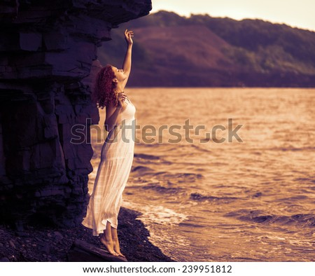 Redhead woman in dress standing on beach and looking to somewhere. Color toned image. - stock photo