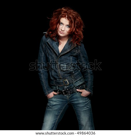 Redhead woman in jeans close up portrait, over black background - stock photo