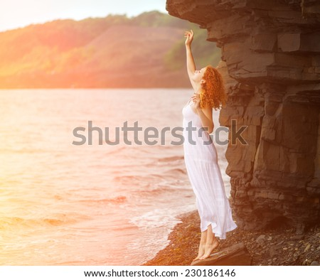 Redhead woman in white dress standing on beach and looking to somewhere. Soft focus. With sunshine effect. Color toned image.  - stock photo