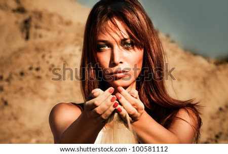 redhead woman outdoor portrait  hands full of sand, summer hot day, front view, small amount of grain added - stock photo