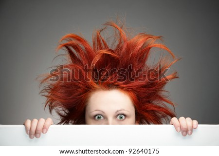 Redhead woman with messy hair against gray background - stock photo