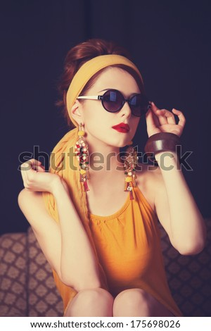 Redhead women sitting in the armchair. Photo in retro color style. - stock photo