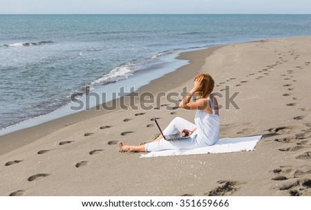redheaded girl working at a laptop sitting on the beach near the sea alone