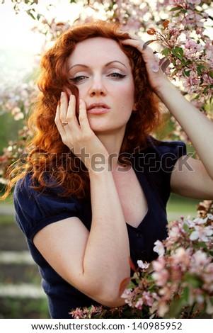 redheaded woman in a spring garden - stock photo