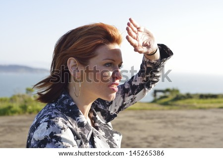 Redheaded woman shielding her eyes from the sunlight - stock photo