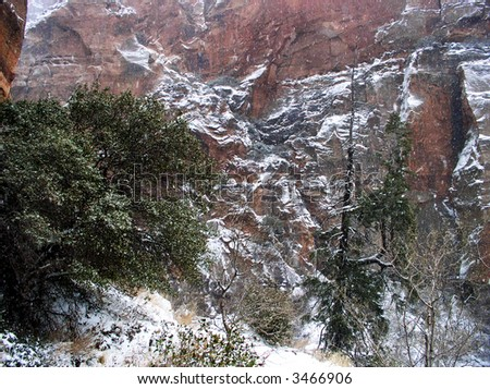redrock canyon walls of desert southwest with snow on cliff face - stock photo