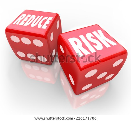 Reduce Risk words on two red dice to illustrate lowering your chances for liability, danger, hazard or exposure while increasing safety and security - stock photo