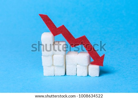 Reducing sugar content in the cow. Diabetes. Stairs of sugar cubes and a red arrow down on a blue background