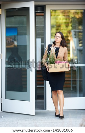 Redundant Businesswoman Leaving Office With Box - stock photo