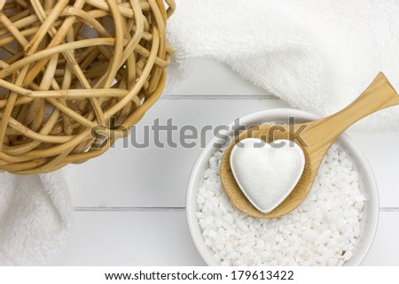 reed ball, wooden spoon with bath bomb in heart shape on bowl filled with bath salt and towel behind it - stock photo