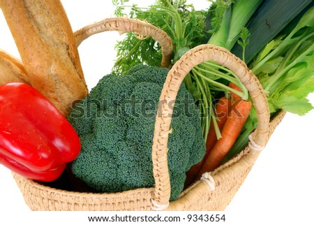 Reed shopping bag with fresh vegetables and french bread on reflective surface, studio shot, white background. - stock photo