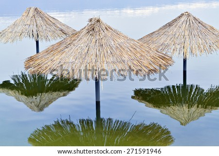 Reed sunshades flooded after heavy rains connected with climate changes - stock photo