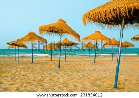 Reed umbrellas on the beach  - stock photo