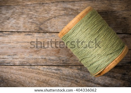 Reel green yarn right side on wood background - stock photo