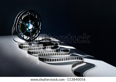 Reel of film on a black background - stock photo