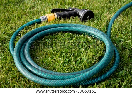Reel of hose pipe and spraying head on grass. - stock photo