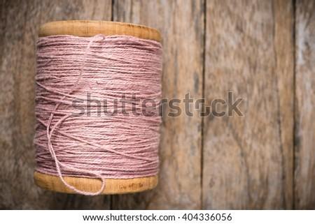 Reel pink yarn left side on wood background - stock photo