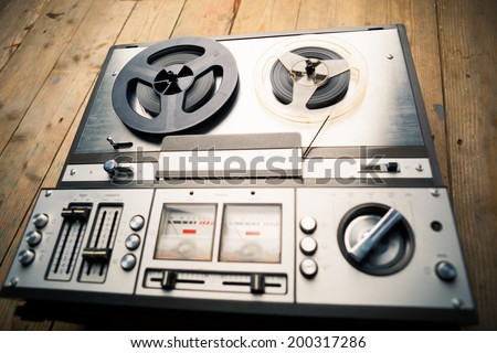 reel to reel tape player and recorder on wooden background - stock photo
