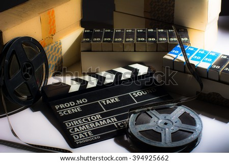 Reel with film and cinema clap. Motion picture films in boxes - stock photo