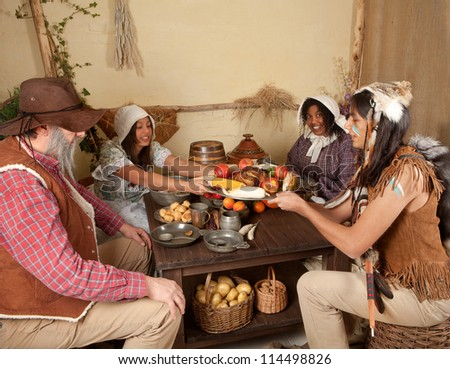 Reenactment scene of the first Thanksgiving Dinner in Plymouth in 1621 with a Pilgrim family and a Wampanoag Indian - stock photo