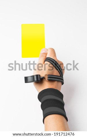 Referee hand and whistle show  Yellow  card to player with white background - stock photo