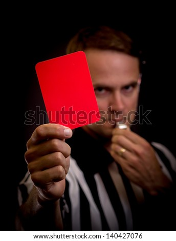 Referee holding red card for foul concept - stock photo