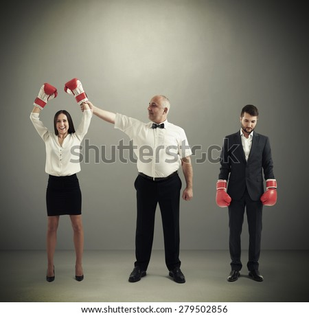 referee holding winner businesswoman in boxer gloves and looking at her, near standing sad loser businessman over dark grey background - stock photo