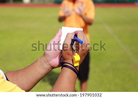 Referee note his paper while holding a yellow card  - stock photo