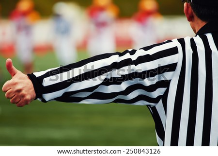 Referee of the american football on the field, american football referee gestures with big team in of focus on background - stock photo