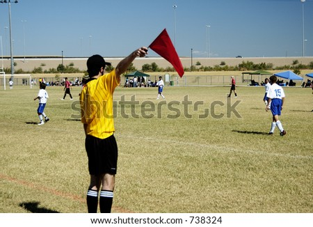Referee signaling from the sidelines of a soccer game.