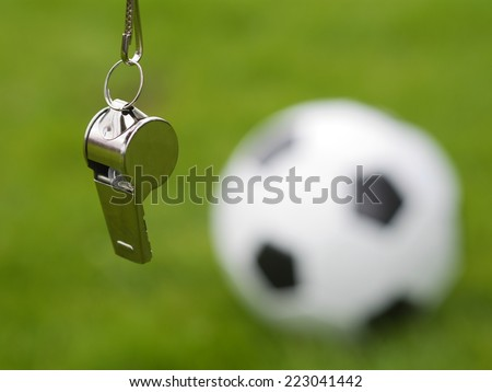 referee whistle in front of soccer ball - stock photo