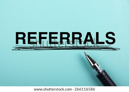 Referrals text is on blue paper with black ball-point pen aside. - stock photo