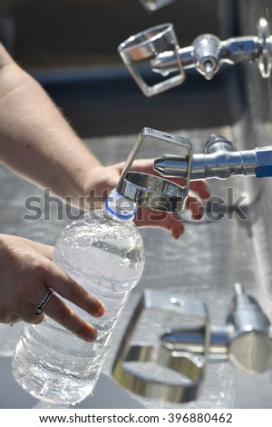 Refilling a plastic water bottle from a tap